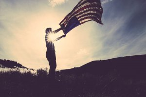 Photo of young man waving flag with sky in background.